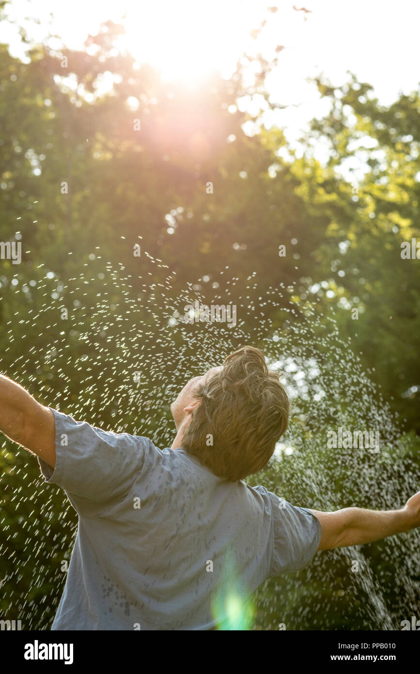 Young mam standing under a spray of water on a hot day with his arms outstretched rejoicing, leafy green tree background. - Stock Image