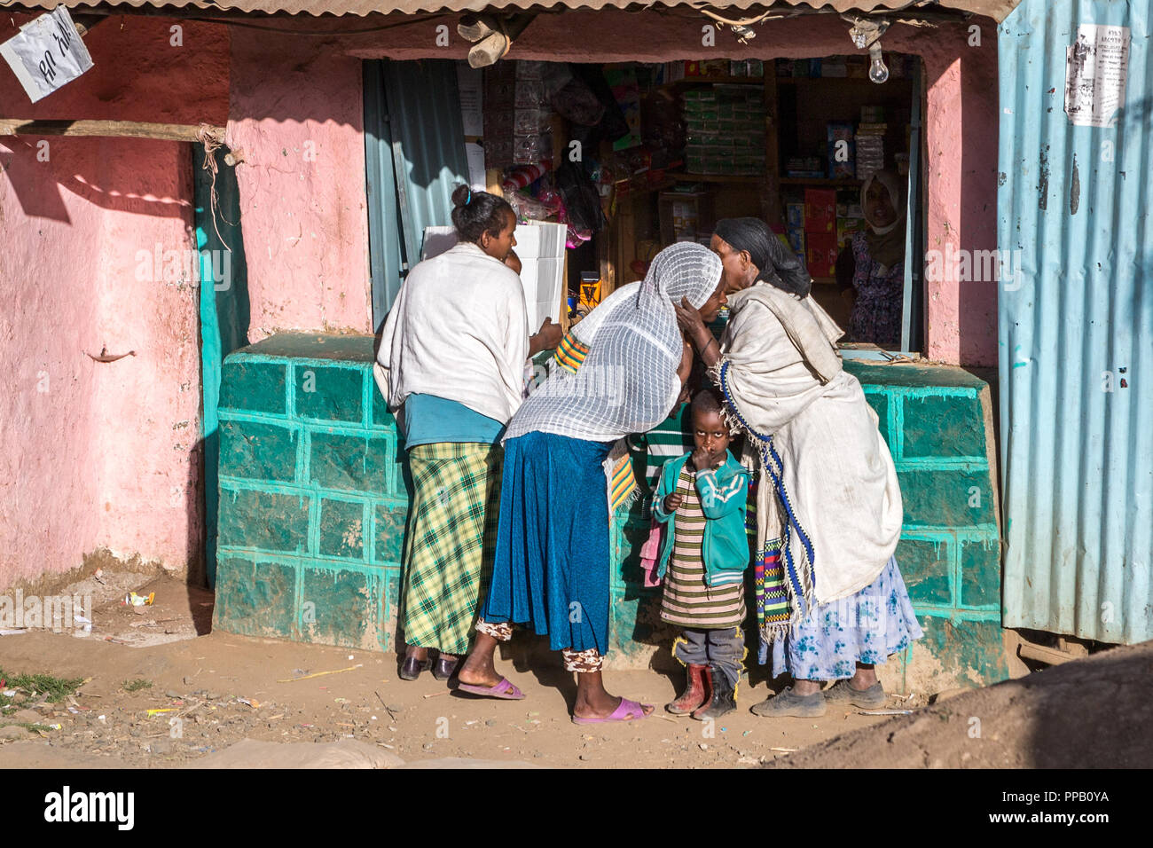 Amhara Region, Village, Ethiopia, Warm embrace by a shop - Stock Image