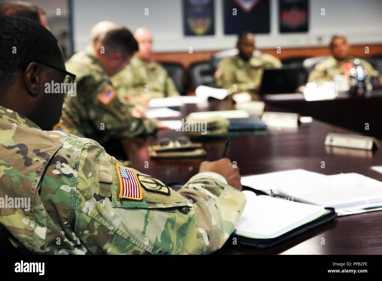 U.S. Army Maj. Julian Milligan, executive officer of the 151st Expeditionary Signal Battalion, 228th Theater Tactical Signal Brigade, South Carolina National Guard, takes notes during a meeting with leaders assigned to the 2d Theater Signal Brigade, Aug. 13, 2018 in Wiesbaden, Germany. Stock Photo