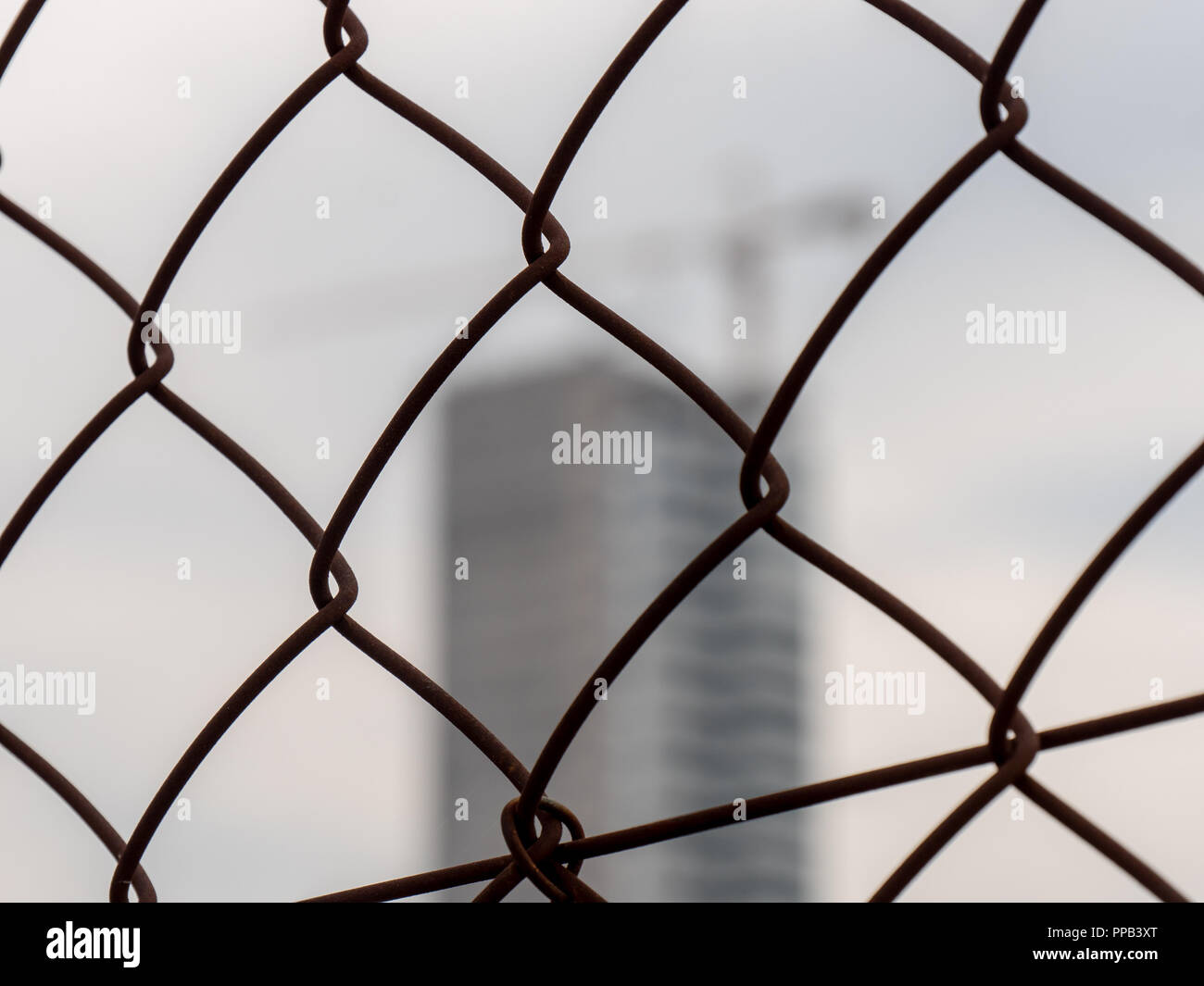 blurred not in focus corporate building behind the cage fence - Stock Image