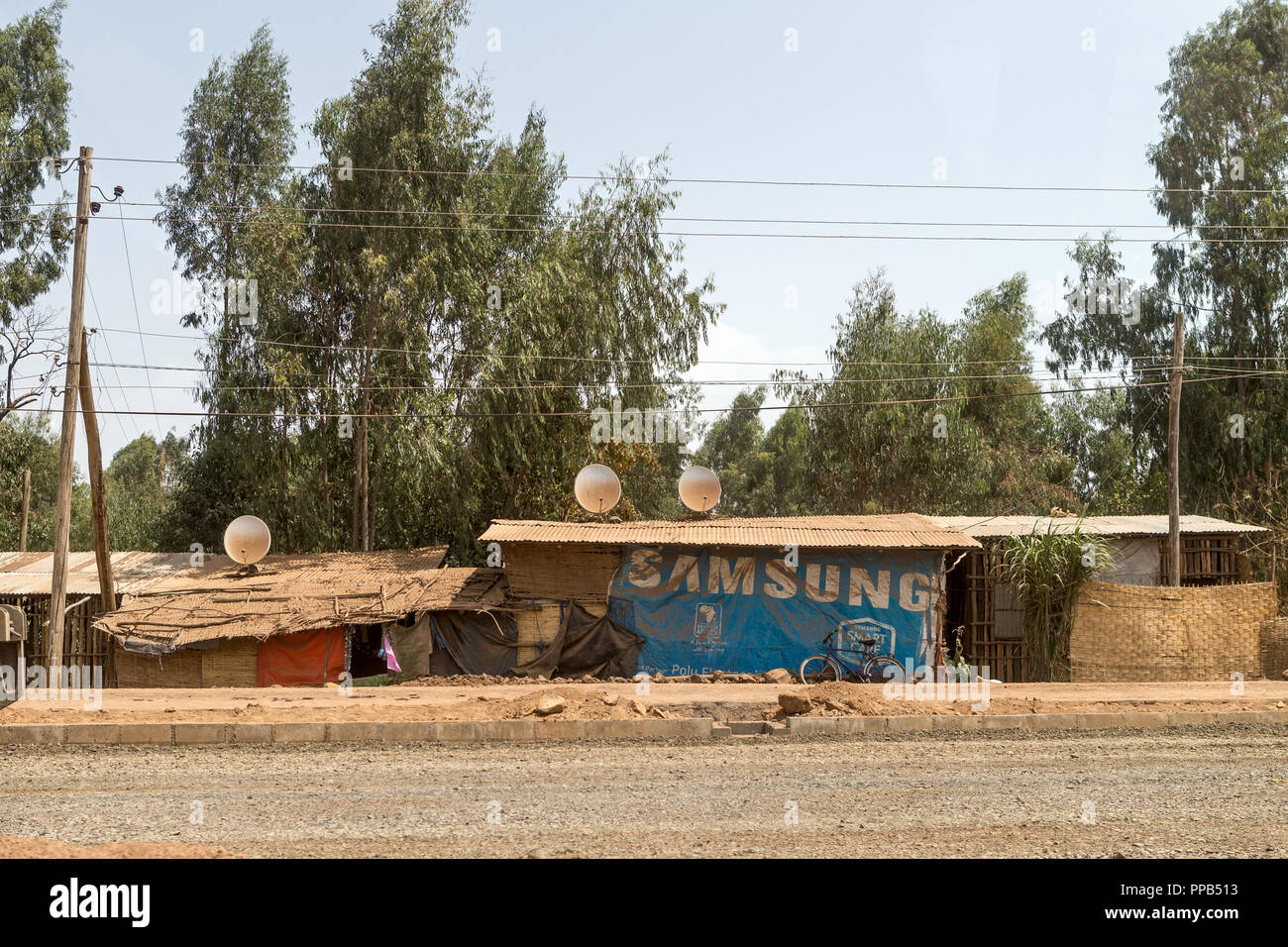Dusty dirt track from Blue Nile to Bahir Dar, Ethiopia - satellite tv shanty homes - Stock Image