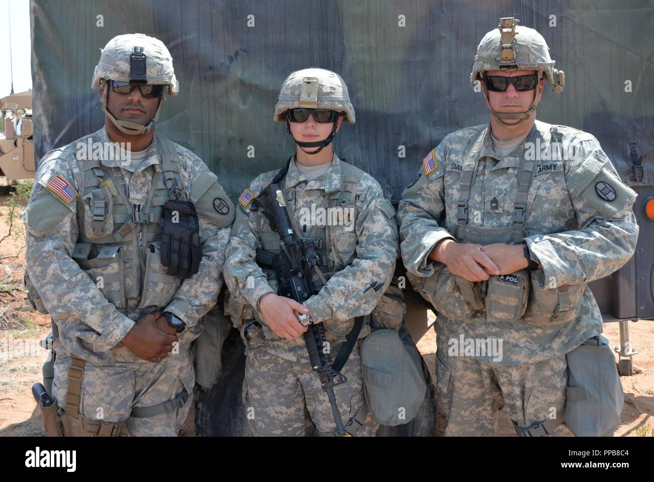"""(Left to right) Capt. Ronald Colvin, Charlie Battery 1-113th Field Artillery Commander, 1st. Lt. Carolyn Horton, and Master Sgt. Brian Dawson. 1st. Lt Horton credits Capt. Colvin and Master Sgt. Dawson as her mentors for making an impact in her success. Charlie Battery, 1-113th Field Artillery Regiment """"Axehandles"""" iis part of the 30th Armored Brigade's eXportable Combat Training Capability (XCTC) exercise with over 4,000 Citizen Soldiers from North Carolina, South Carolina, West Virginia, Minnesota, and the country of Moldova. All will hone their combat skills of """"Shoot, Move, Communicate, an - Stock Image"""