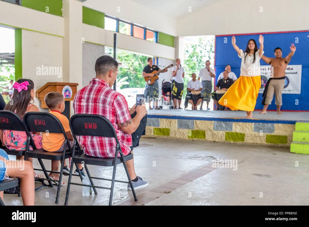 BARRIGADA, Guam (Aug. 18, 2018) Chief (select) Builder John Hart records performers from the group Tao Tao Tano, who are performing Chamorro music and dances during the Village of Barrigada's welcome fiesta for the 30th Naval Construction Regiment (30NCR). The Village of Barrigada is 30NCR's sister village and the two will conduct community service projects and other functions together. 30NCR relocated to Guam from Port Hueneme, California, July 1. - Stock Image