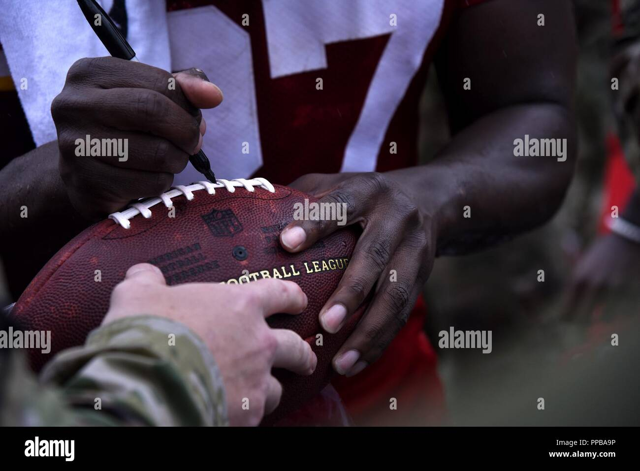 A Kansas City Chiefs player signs a football after military  hot sale
