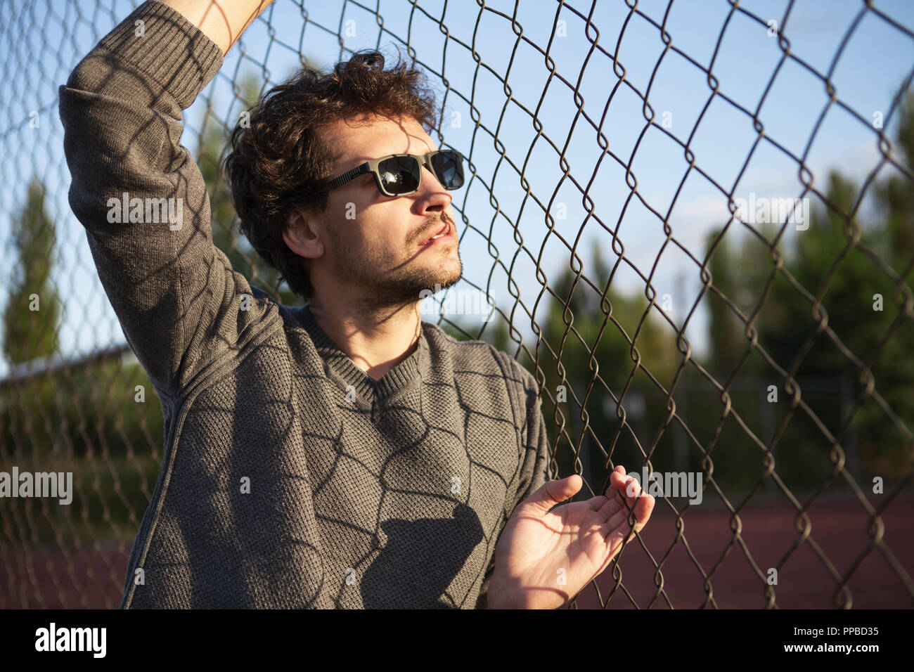 Young man standing and holding the iron fence - Stock Image