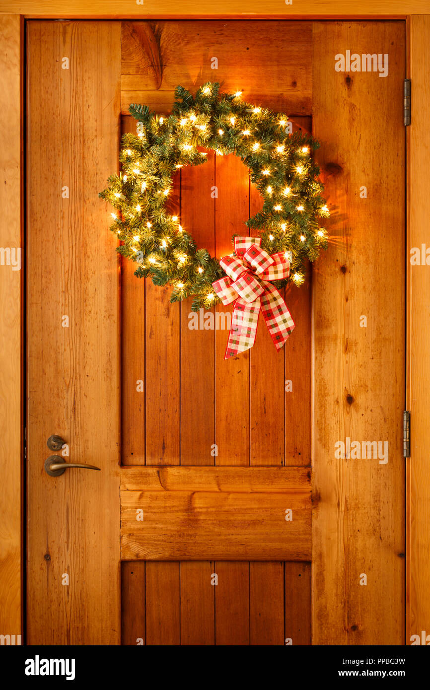 beautiful christmas decorations wreath with ribbon bow and lights on wooden front door background simple rustic country style holiday home decor