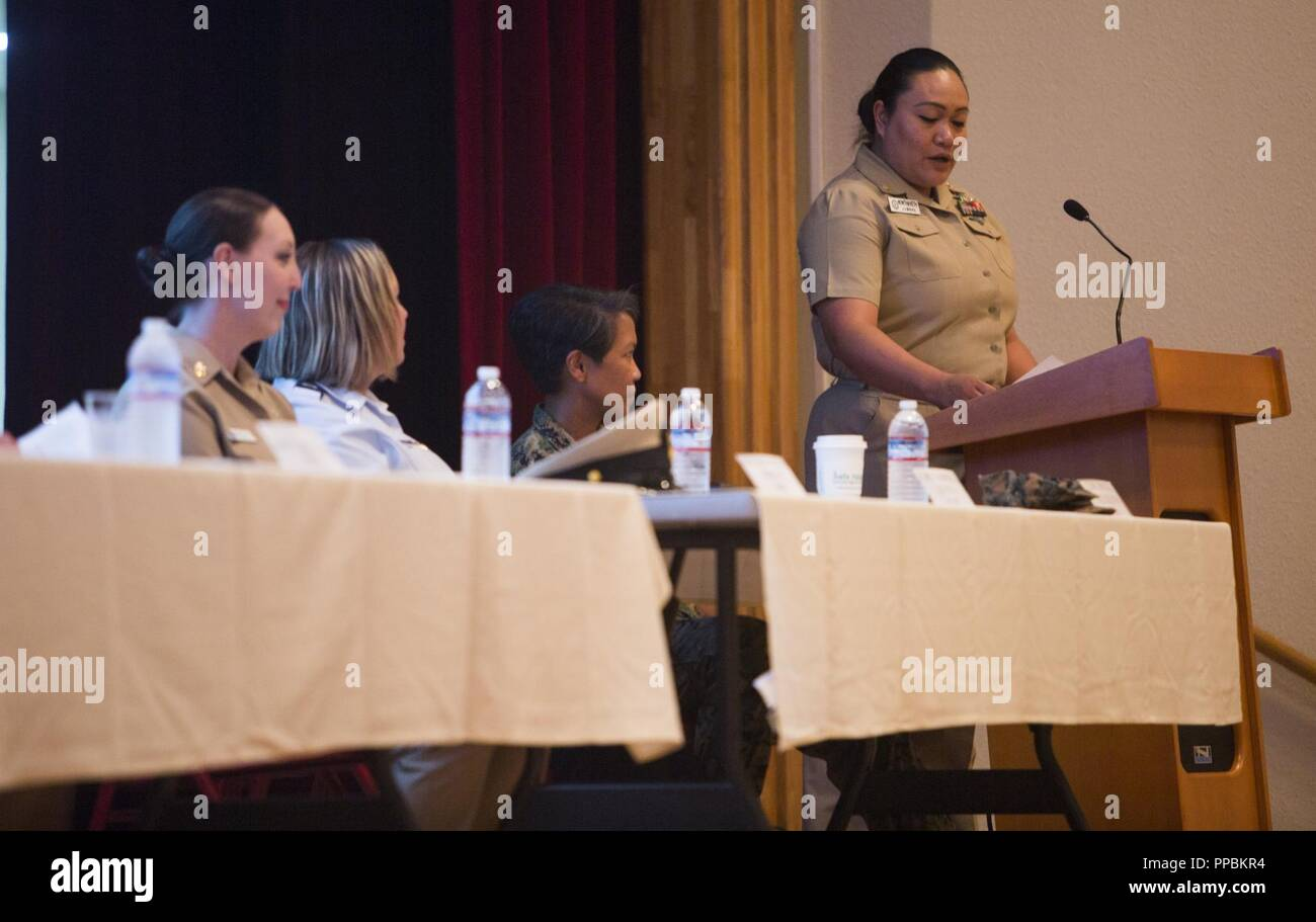 HMC Jane J. Nonthaveth, right, reads questions for a panel of active and retired servicewomen to answer during the Women's Symposium Aug. 30, 2018 at Camp Foster, Okinawa, Japan. The symposium promoted gender equality, empowerment and raised awareness of equal opportunity resources. Nonthaveth, the chief hospital corpsman with Naval Hospital Okinawa, is a native of Denver, Colorado. - Stock Image