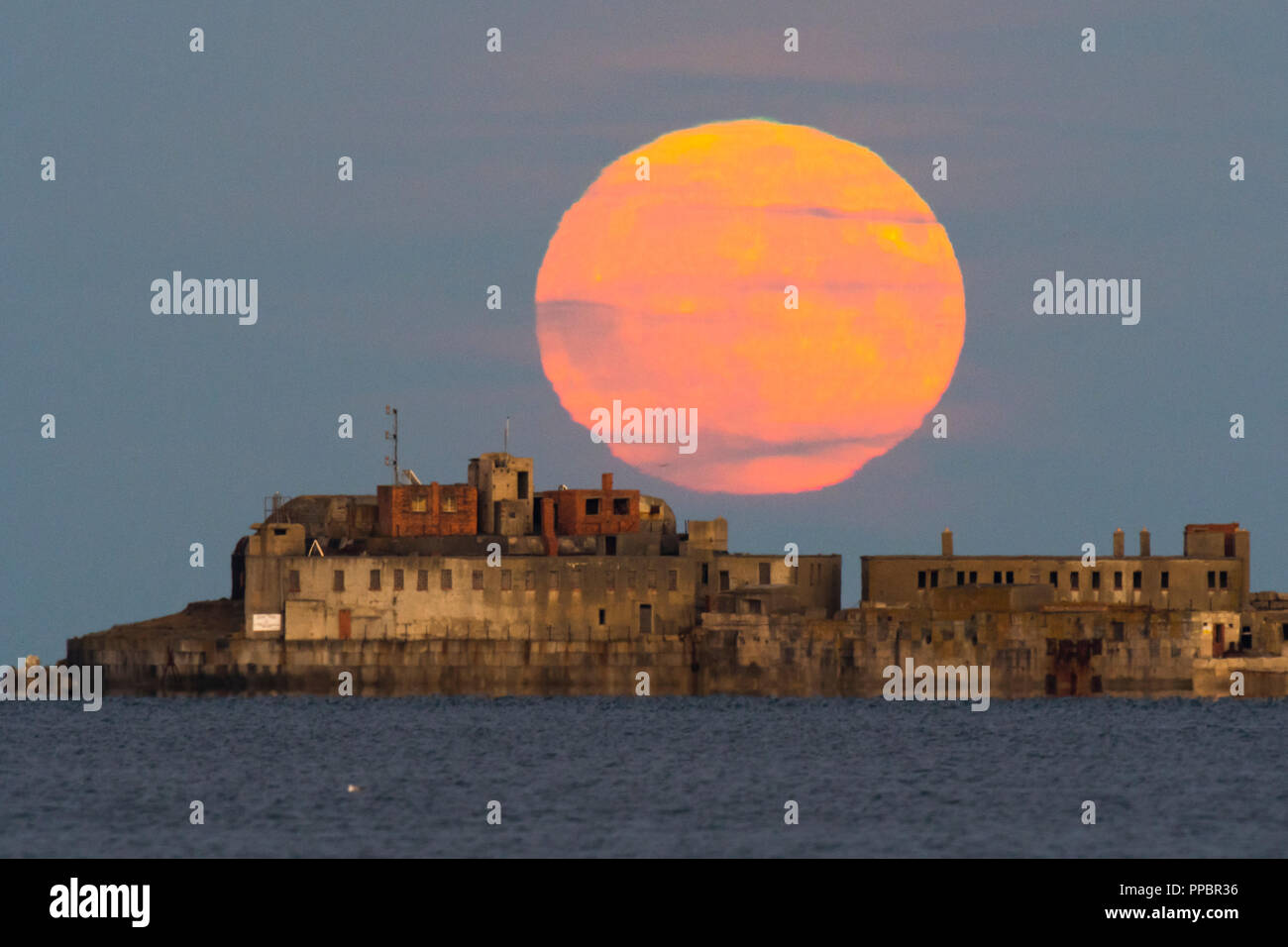 Weymouth, Dorset, UK.  24th September 2018.  UK Weather.  The Harvest Moon rises up from behind the historic 19th century Portland Breakwater Fort on the outer breakwater of Portland Harbour in Dorset.  The now derelict fort also known as Chequered Fort was constructed between 1868 and 1878 and is Grade II listed.  Picture Credit: Graham Hunt/Alamy Live News - Stock Image