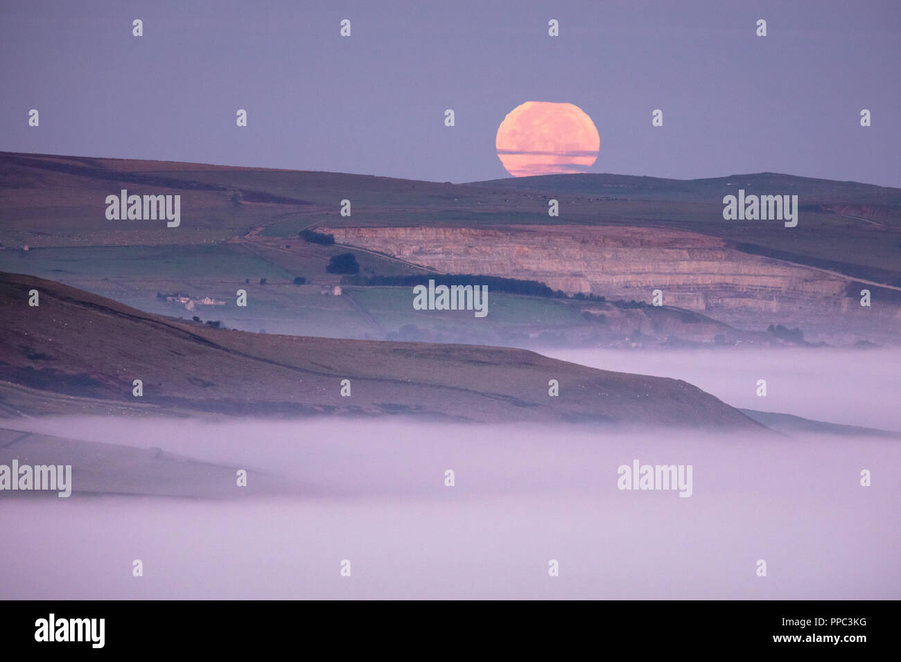 Hope Valley, Derbyshire, UK. 25th Sep 2018. The Full Moon sets over a mist-filled Hope Valley in The Peak District National Park in the early hours of 25th September 2018. Known as the Harvest Moon, the closest full moon to the Autumnal Equinox, it picks up an orange tinge from the sun rising in the opposite side of the sky. Credit: Graham Dunn/Alamy Live News - Stock Image