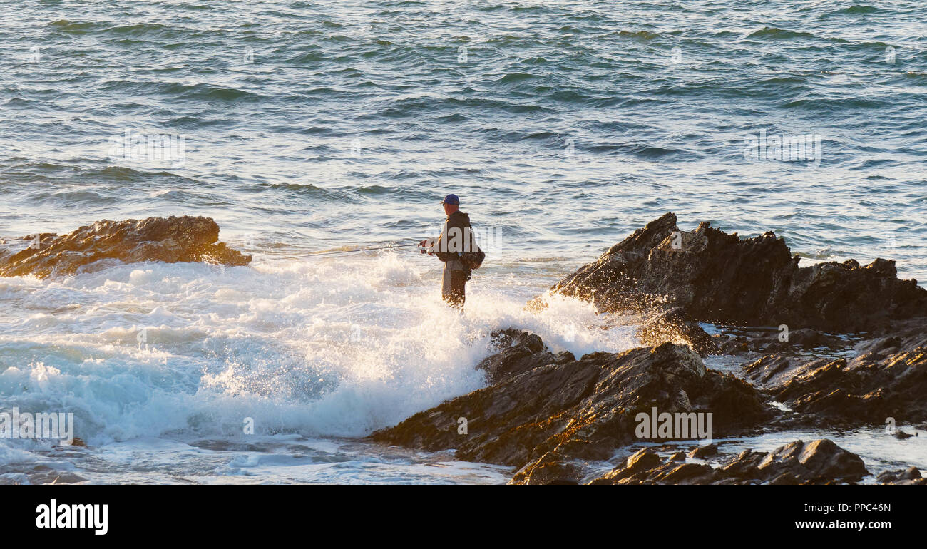 Newquay, Cornwall. 25th Sep 2018. UK Weather, Spring tide sea angler at Fistral Bay takes fishing to the white knuckle sport category as the high spring tide surrounds his extreme spot, defying unpredictable conditions. UK 25th, September, 2018 Credit: Robert Taylor/Alamy Live News Stock Photo