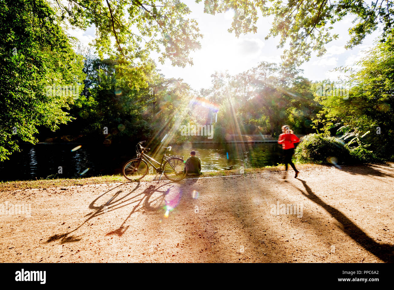 25 September 2018, Berlin: A woman sits next to her bicycle at the Landwehrkanal in the Tiergarten in the evening sun, while a jogger passes by. (Wiping effect due to long exposure time) Photo: Christoph Soeder/dpa - Stock Image