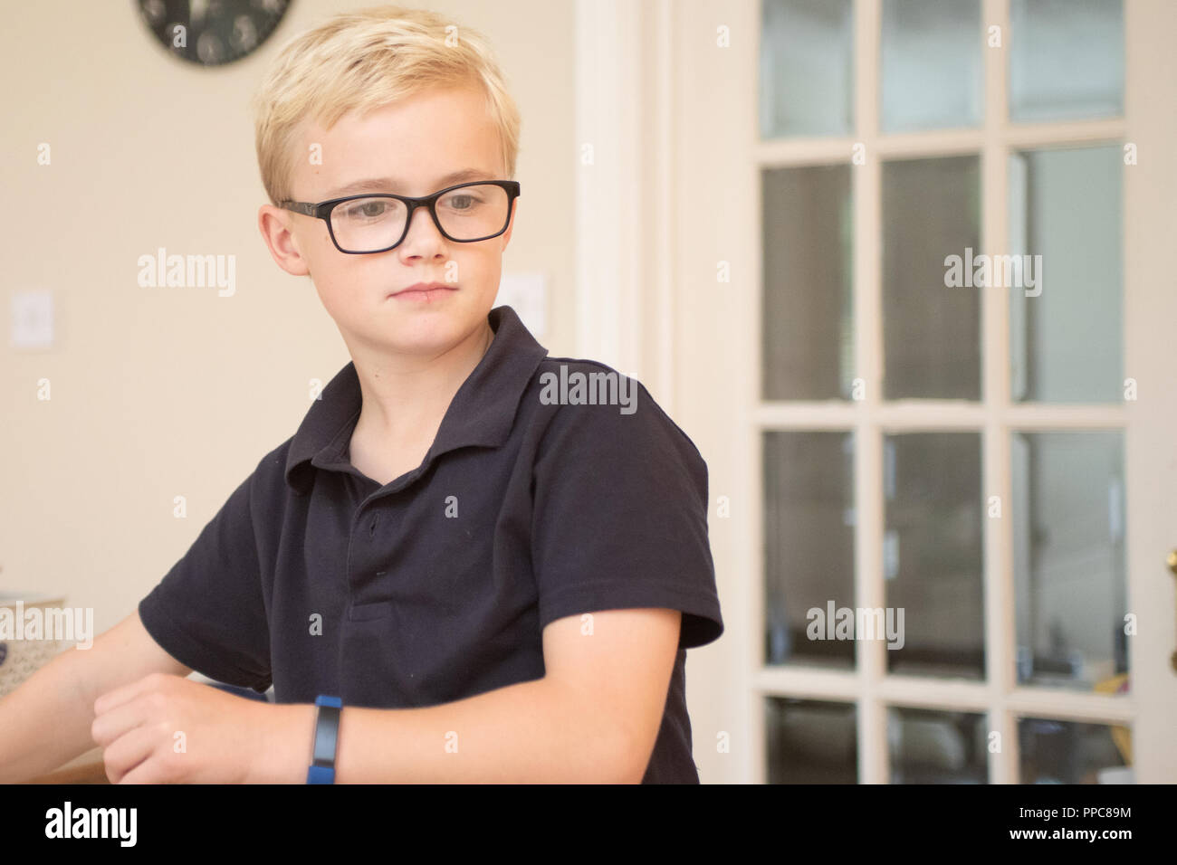 boy wearing glasses white glass door in background - Stock Image