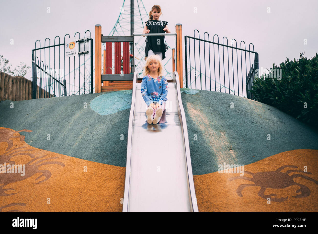 blonde girl play on slide in play park Stock Photo