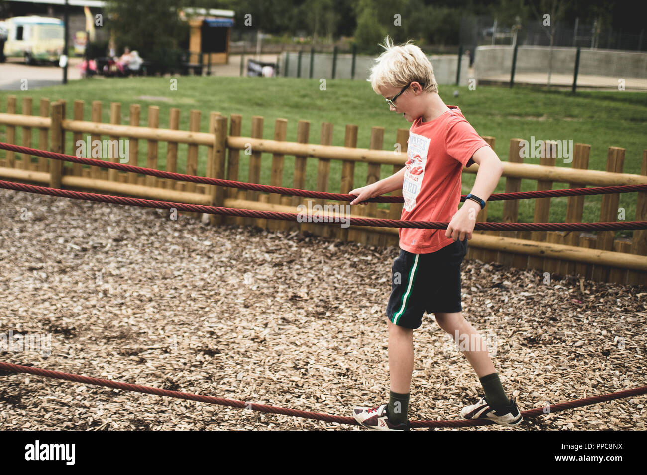 blond boy playing on a play park - Stock Image