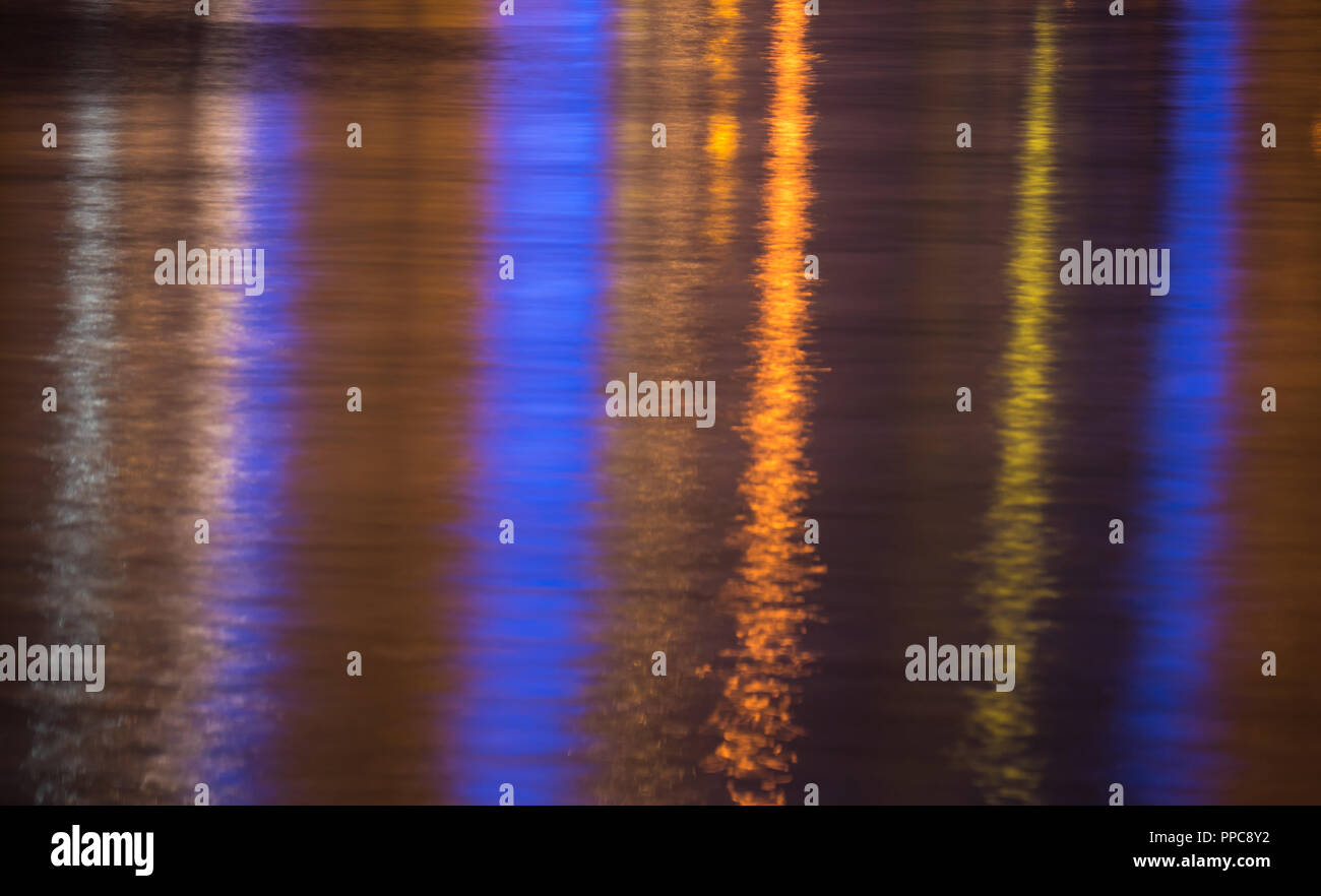 Lights reflecting in rippled sea water surface - Stock Image