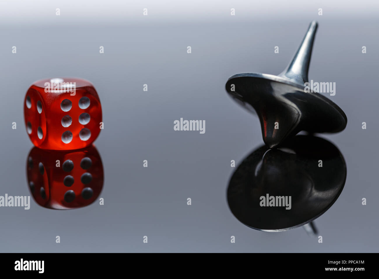 Whirligig and dice with reflection on a dark background - Stock Image