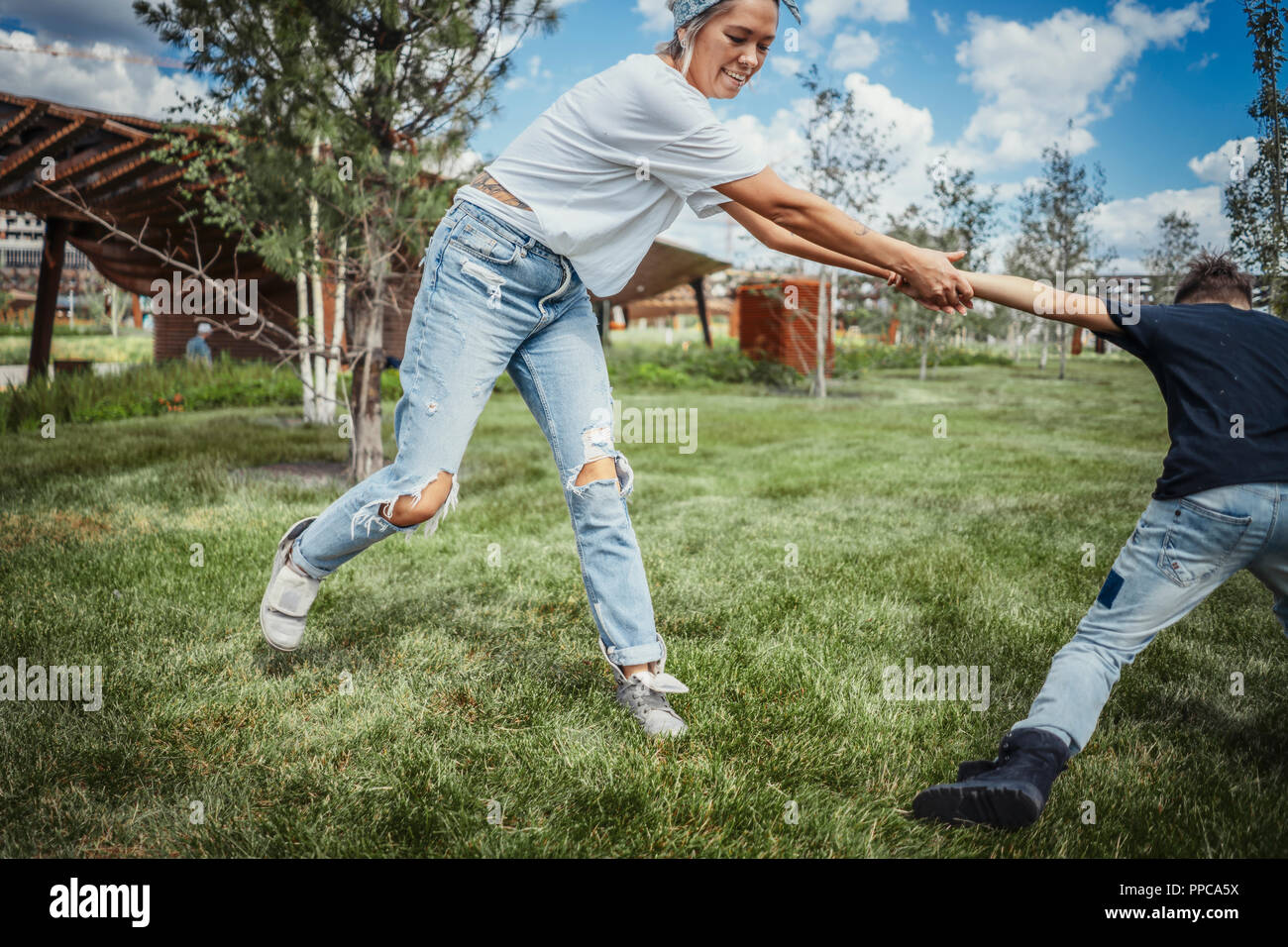 Young mum turning around, whirling with her sons at park. Happy family concept. - Stock Image