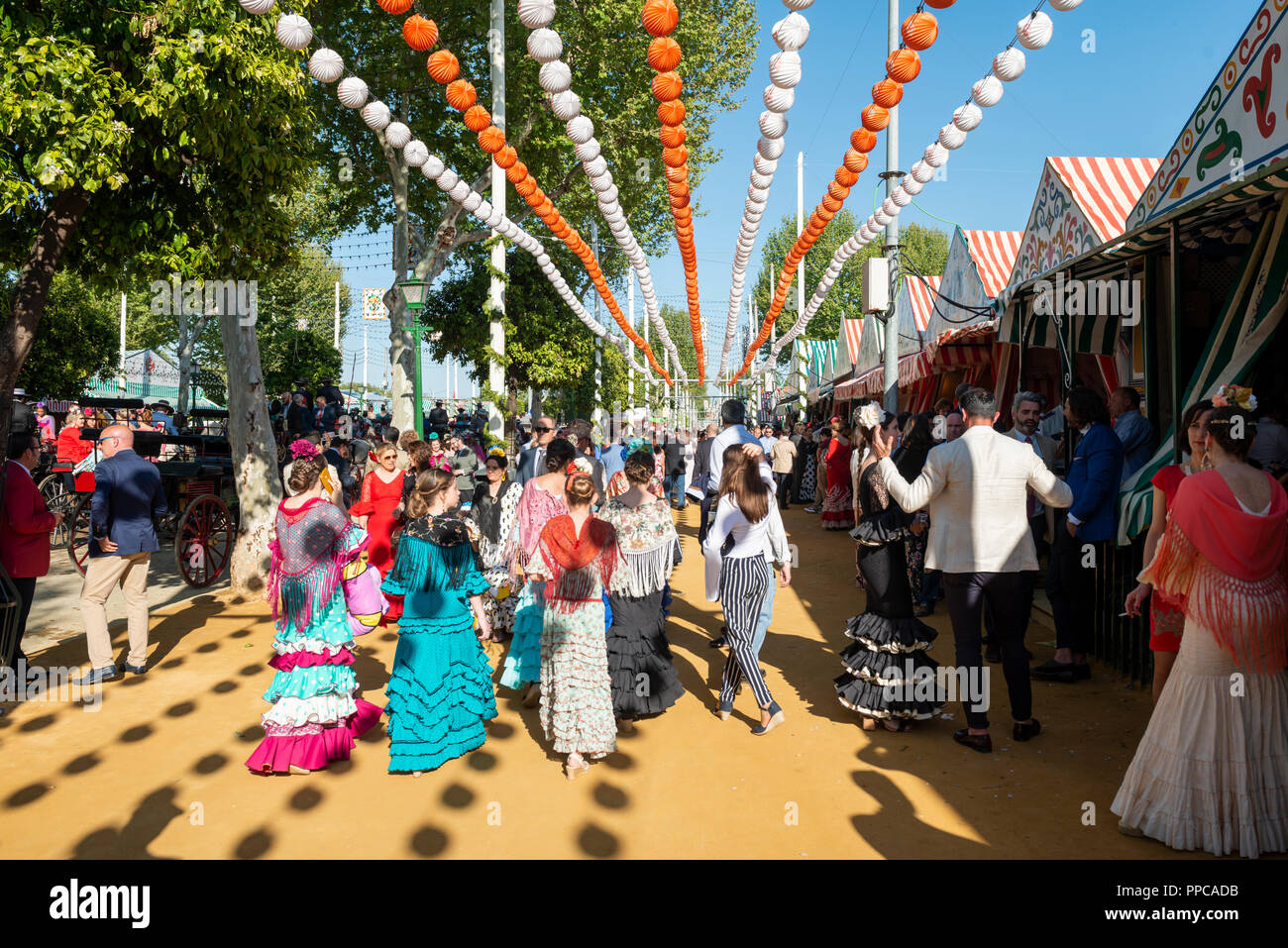 Spanish women with colorful flamenco dresses in front of marquees, Casetas, Feria de Abril, Sevilla, Andalusia, Spain Stock Photo