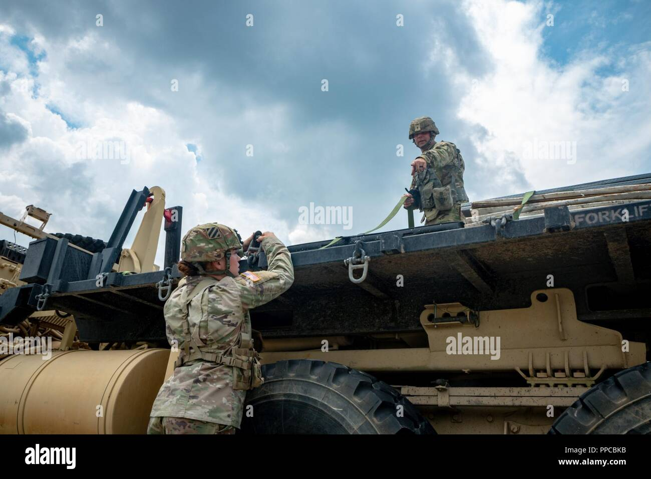 "Sgt. Wayne Coats and Pfc. Amanda Blanton of Delta Forward Support Company, 6th Squadron, 8th Cavalry Regiment, 2nd Armored Brigade Combat Team, properly secure resupply equipment to a M1077 A1 Flatrack, August 13, at Fort Stewart, Ga. ""How will our Soldiers fight without ammunition, food, or water?"" said Sgt. Coats. ""A team is like a clock. There are continuous gears inside of that clock, and we are one of those gears in motion."" - Stock Image"