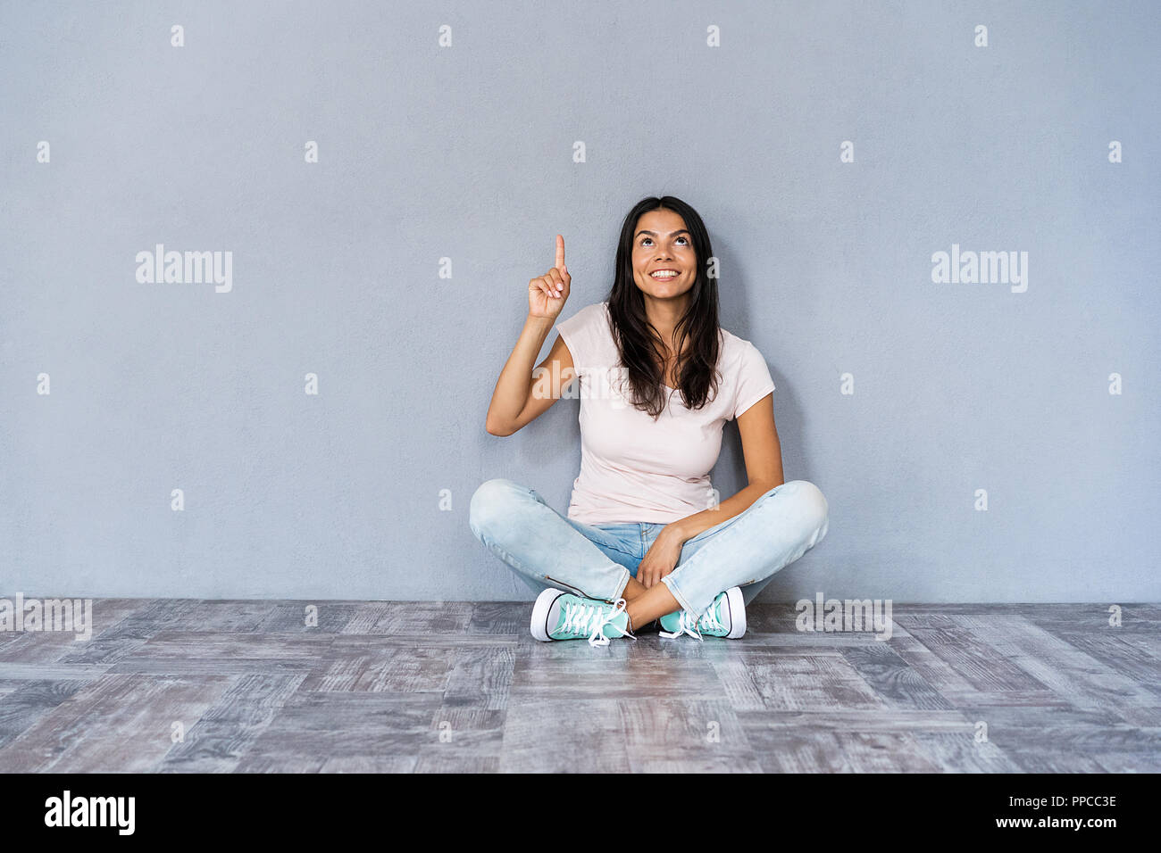 Have idea! Cute woman in casual clothes sitting with legs crossed on the floor gesturing index finger up, meaning eureka over grey wall. - Stock Image