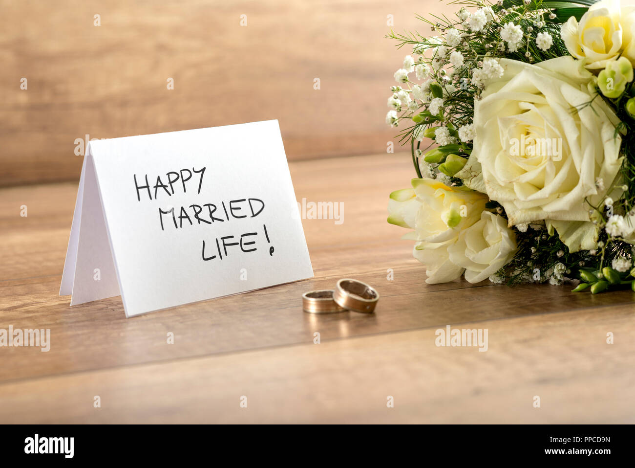 Close up of Beautiful Bride Bouquet of  Fresh Flowers, Pair of Rings and Happy Married Life Card for Newlyweds on Top of Wooden Table. - Stock Image