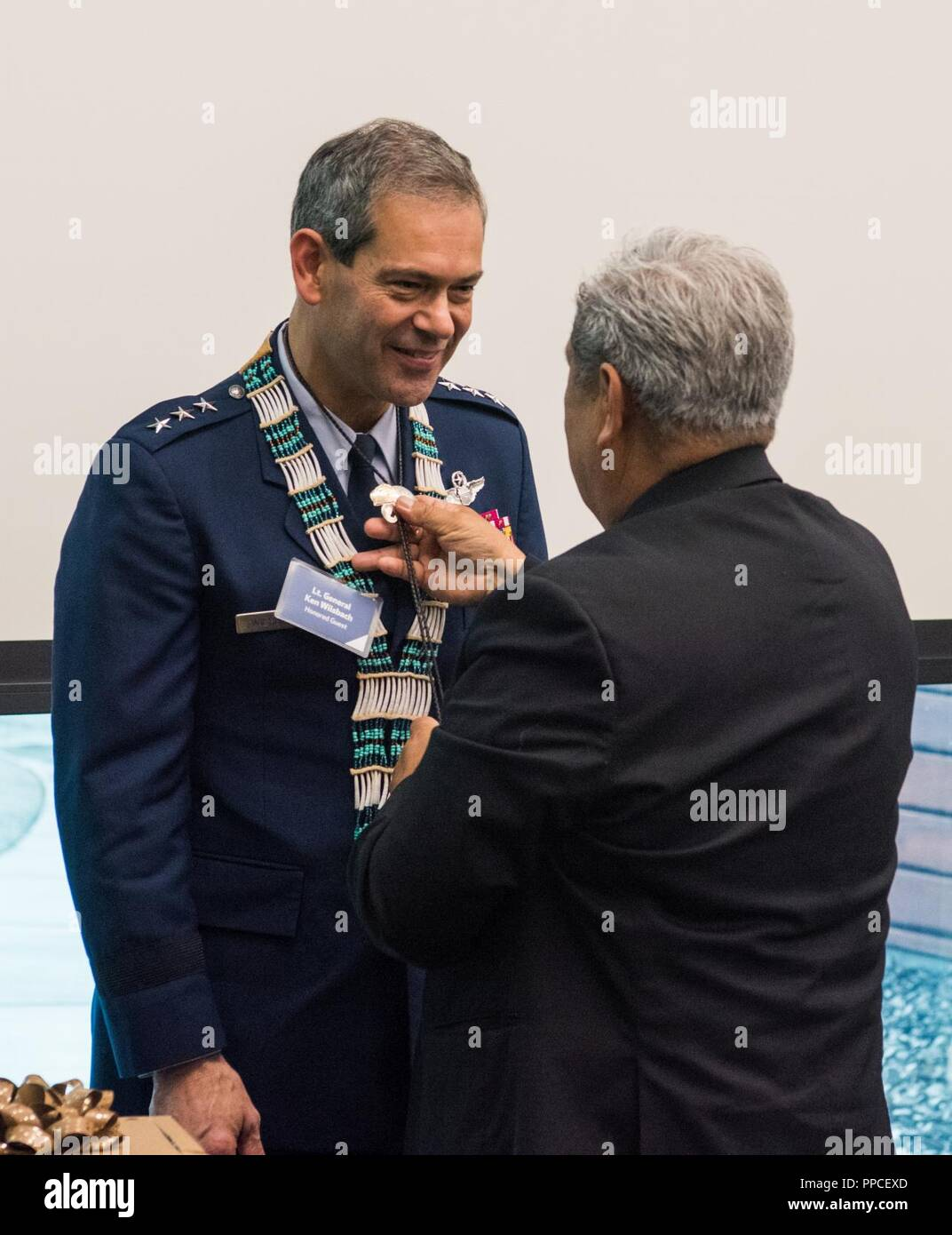 An Alaskan Federation of Natives council member presents a bolo tie to U.S. Air Force Lt. Gen. Ken Wilsbach, commander of Alaskan NORAD Region, Alaskan Command and Eleventh Air Force, during a Native Alaska naming ceremony at the Fireweed Convention Center in Anchorage, Alaska, Aug. 21, 2018. AFN hosted the unique event honoring Wilsbach for his service and involvement with Native Alaskan communities during his tenure in Alaska. It marked the first time in Alaska Native history a U.S. Armed forces general officer was given multiple Native names. - Stock Image