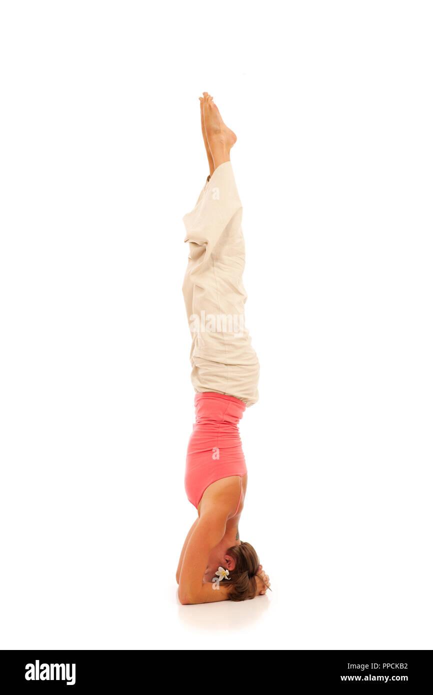 Young woman doing yoga Headstand Pose - Stock Image