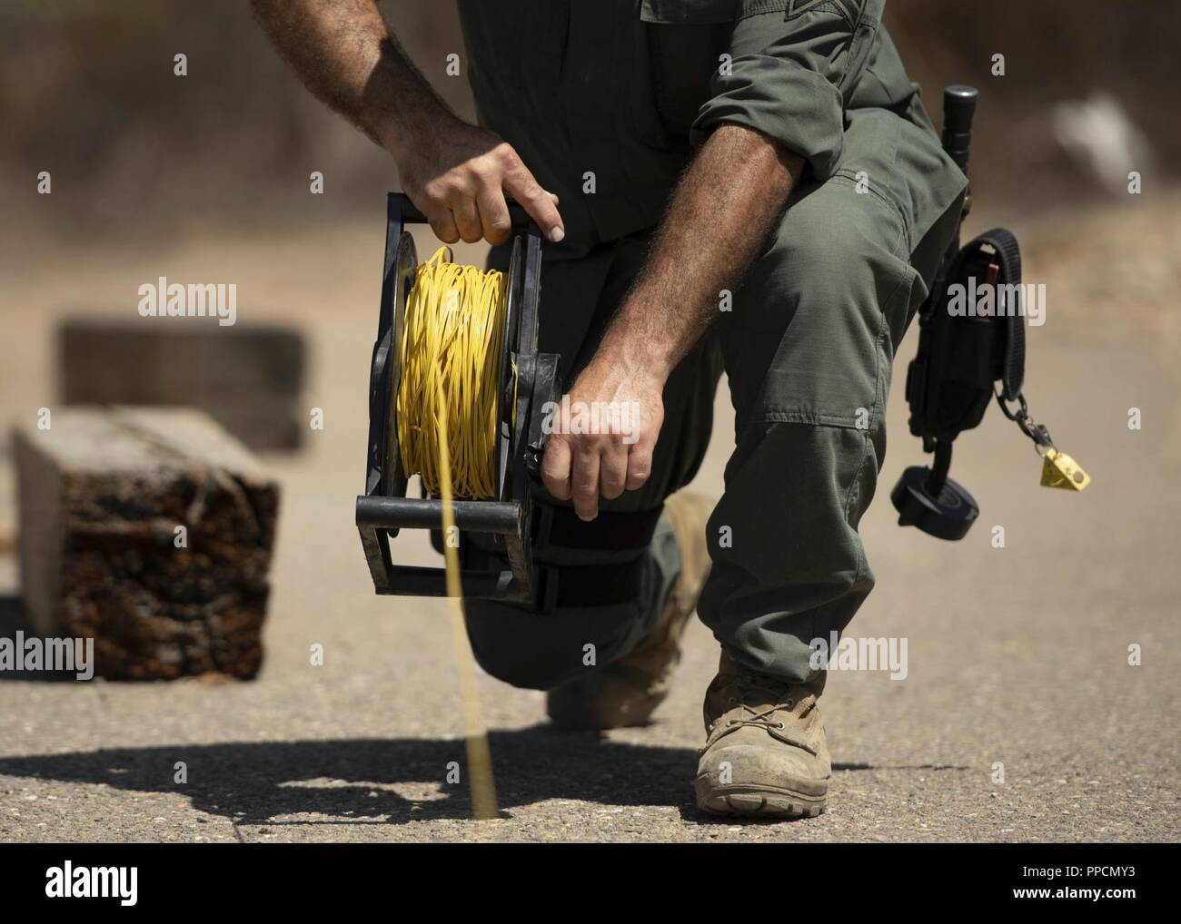 A bomb technician reels in a fuse used to ignite explosions