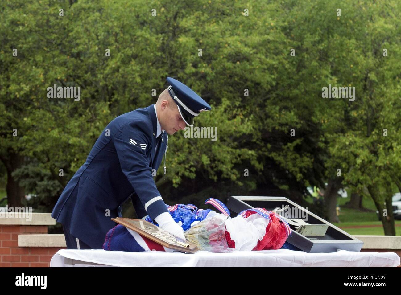 Senior Airman Zachary, Offutt Air Force Base Honor Guard member, lays a wreath and roses next to a piece of C-130 wreckage from 60528, an aircraft which was shot down in the Cold War, during a remembrance ceremony held Aug. 30, 2018, at Offutt Air Force Base, Nebraska. The ceremony was attended by members of the 97th Intelligence Squadron, the Prop Wash Gang, a group of retired ISR operators, family members and fellow wingman to the fallen. - Stock Image