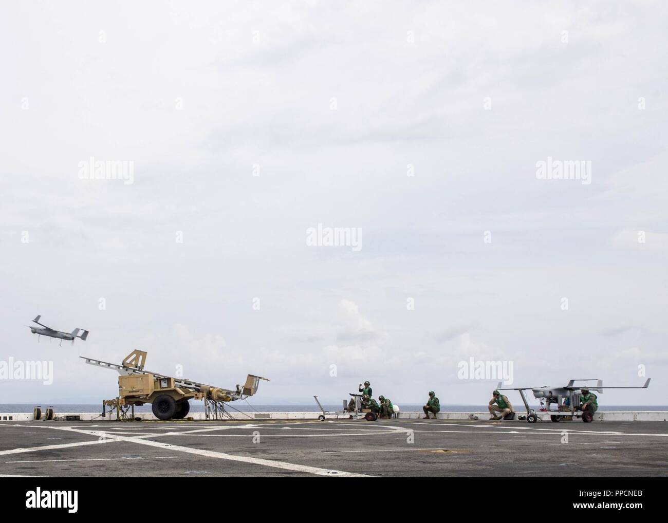 SURIGAO STRAIT (Aug. 16, 2018) Marines assigned to the Marine Light Attack Helicopter detachment of Marine Medium Tiltrotor Squadron VMM (166), launch an RQ-21A Blackjack drone, from the flight deck of San Antonio-class amphibious transport dock USS Anchorage (LPD 23) during a regularly scheduled deployment of the Essex Amphibious Ready Group (ARG) and 13th Marine Expeditionary Unit (MEU). The Essex ARG/13th MEU is a capable and lethal Navy-Marine Corps team deployed to the 7th fleet area of operations to support regional stability, reassure partners and allies and maintain a presence postured - Stock Image