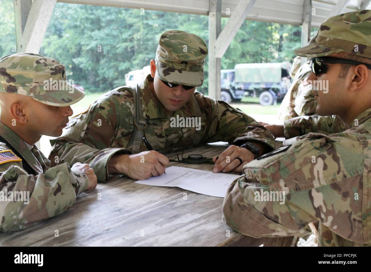 U.S. Army Sgt. Guillermo Ortiz of San Juan, Puerto Rico, a team leader with the 246th Quartermaster Company, locates a point on a map as part of a land navigation test at Fort Pickett, Va., Aug. 12, 2018. More than 300 Army Reserve Soldiers from across the nation attended the Mortuary Affairs Exercise, which also included marksmanship, search and recovery operations and other training. - Stock Image
