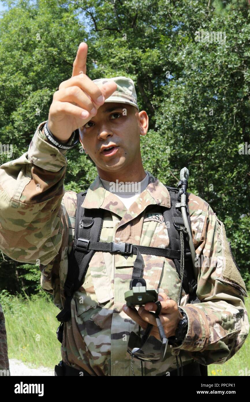 U.S. Army Spc.Michael A. Lopez of Guanica, Puerto Rico, a mortuary affairs specialist for the 246th Quartermaster Company, points the way for his team during a land navigation test at Fort Pickett, Va., Aug. 12, 2018. More than 300 Army Reserve Soldiers from across the United States attended the Mortuary Affairs Exercise, which also included marksmanship, search and recovery operations and other training. - Stock Image