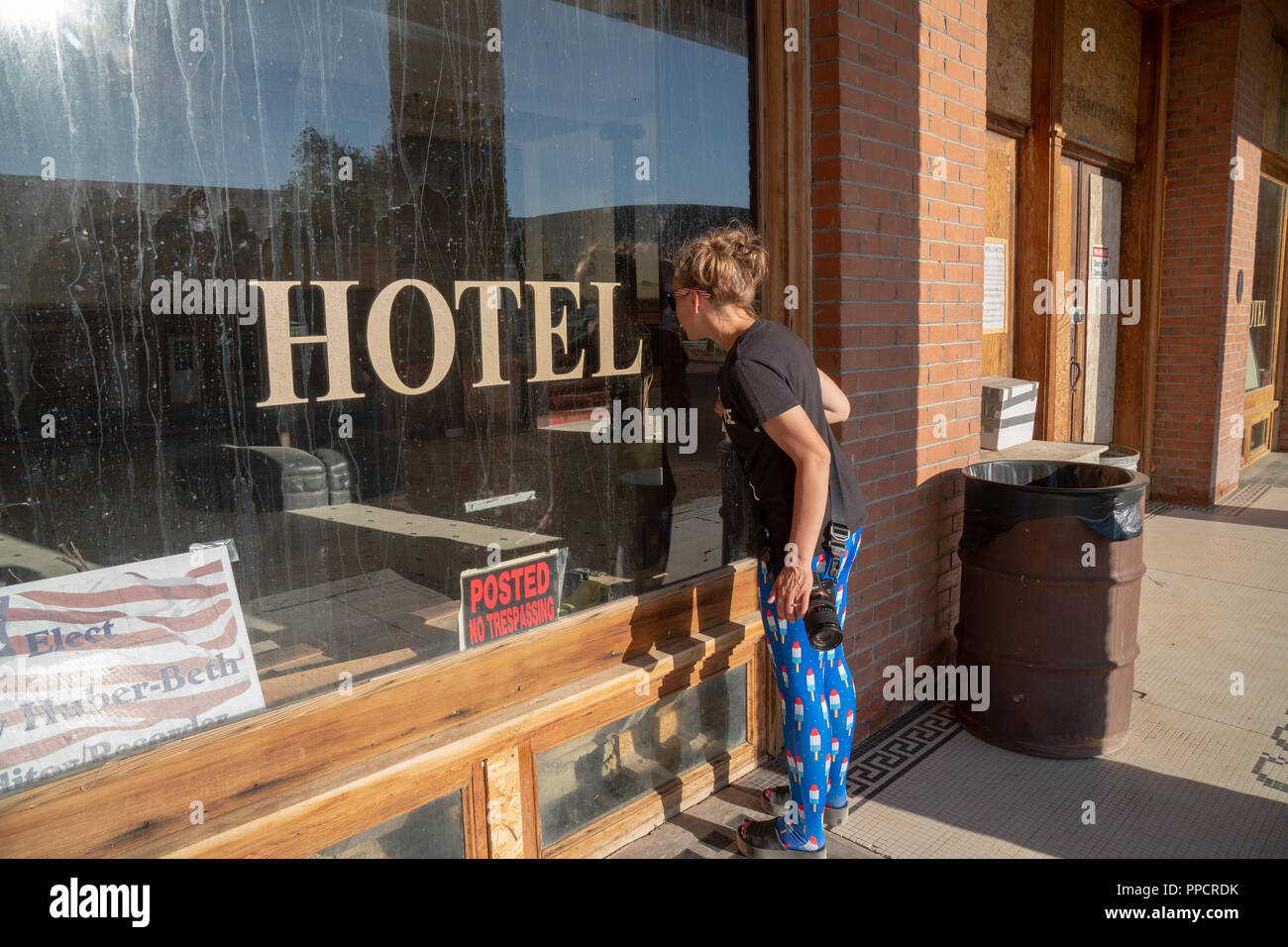 GOLDFIELD, NEVADA: A curious woman peers through the window of the abandoned and supposedly haunted Goldfield Hotel, an historic building along US 95 - Stock Image