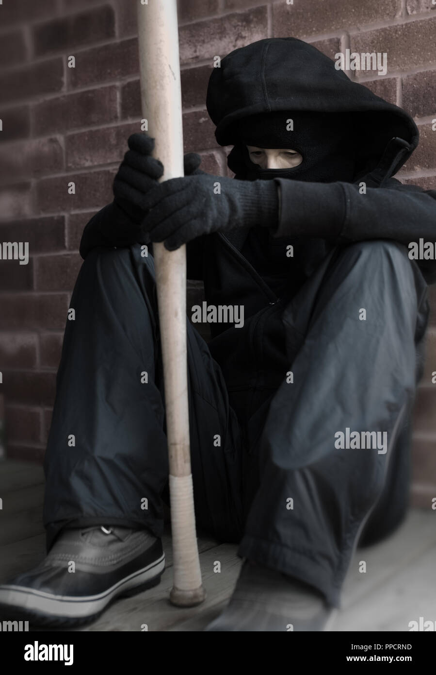 A rioter ready for troubles, is waiting with a baseball bat in his hands, ready for attack. Stock Photo