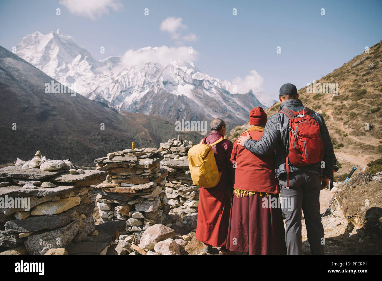 Two Buddhist monks pose with a Himalayan trekker in the Everest Region. - Stock Image