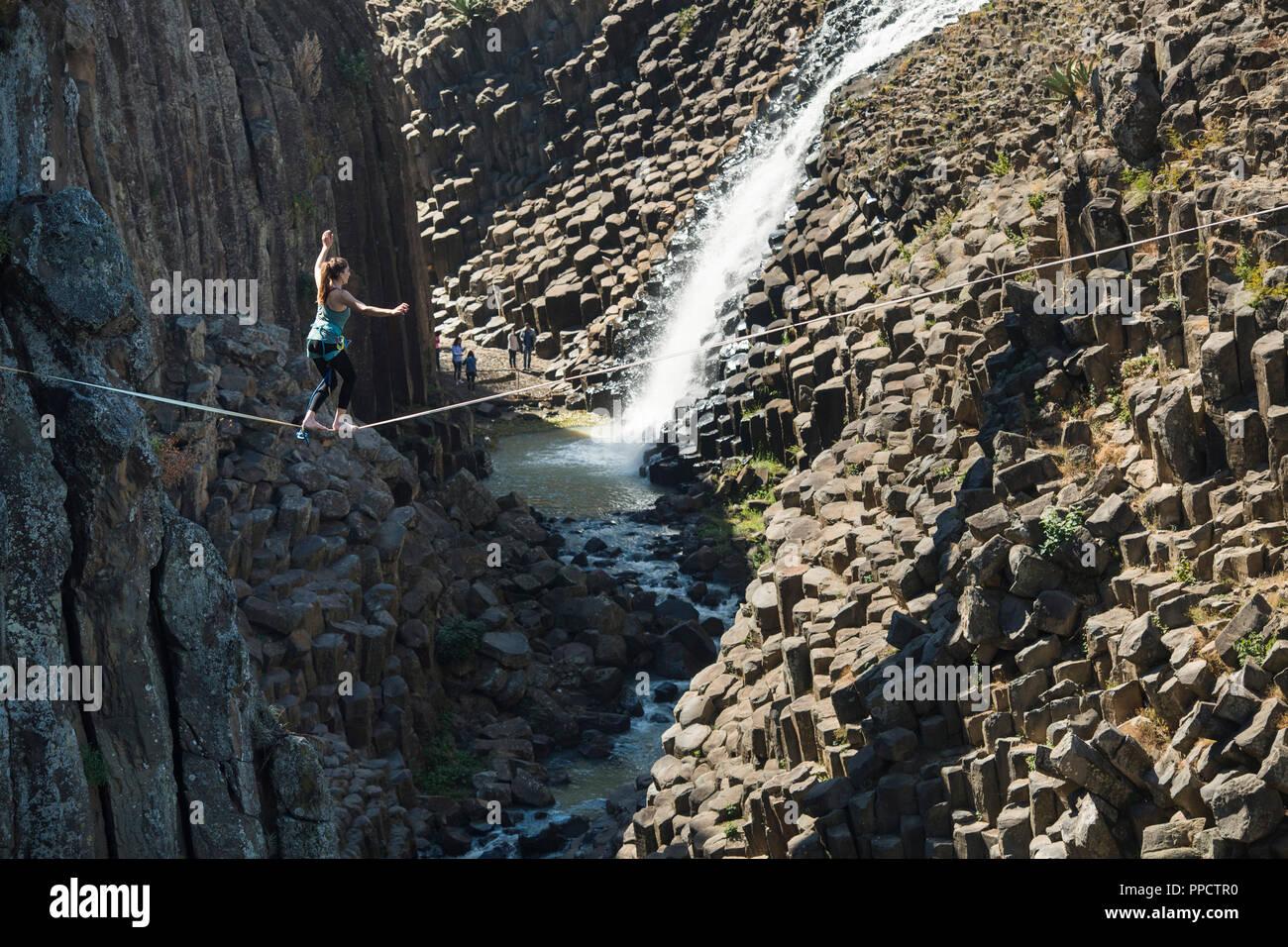 Young woman balancing on tightrope across Basaltic Prisms of Santa Maria Regla, Huasca de Ocampo, Hidalgo, Mexico - Stock Image