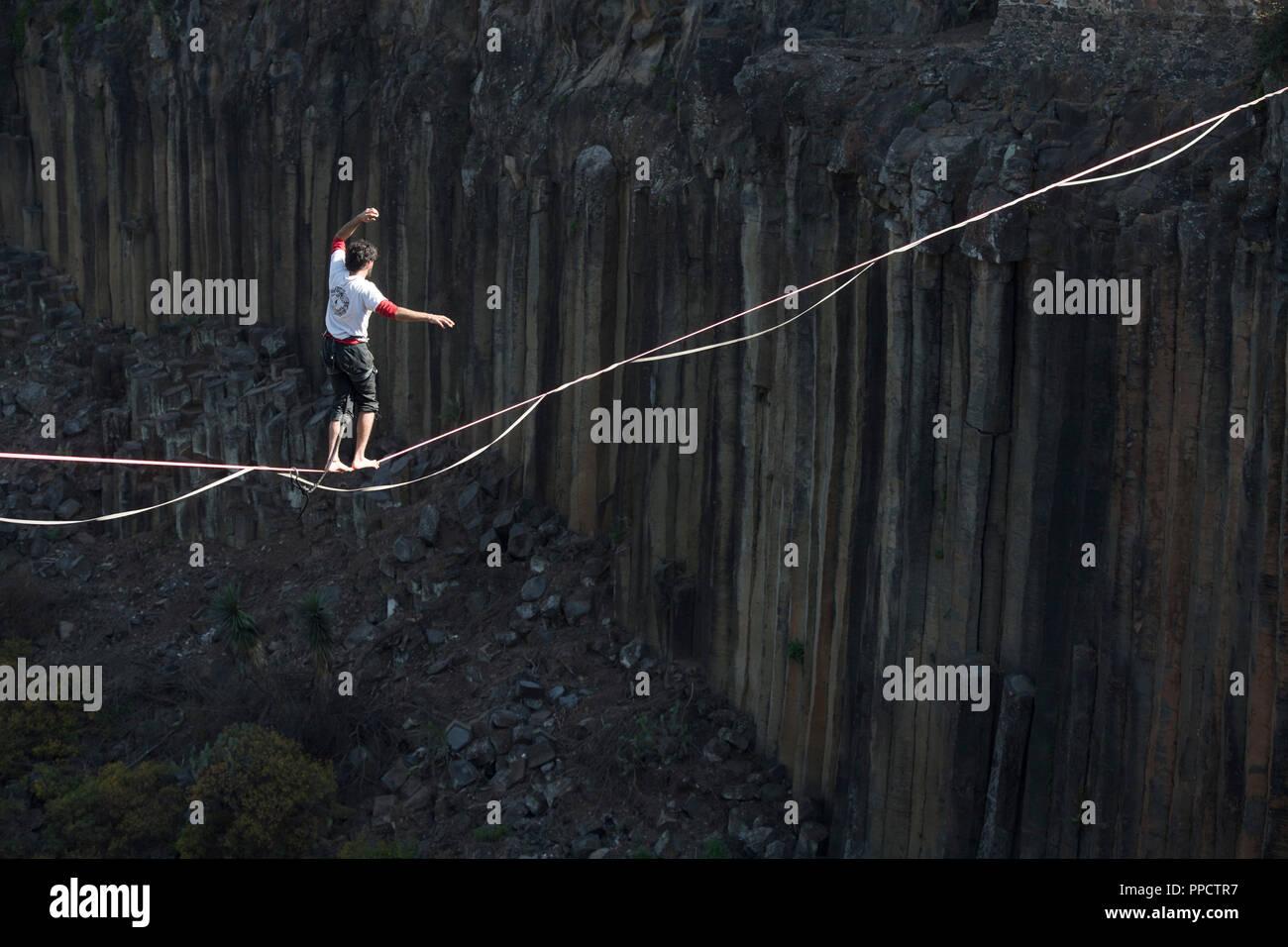 Man balancing on tightrope across Basaltic Prisms of Santa Maria Regla, Huasca de Ocampo, Hidalgo, Mexico - Stock Image