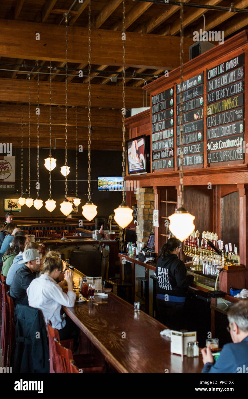 People talking and relaxing at bar under hanging light fixtures, Seattle, Washington, USA - Stock Image