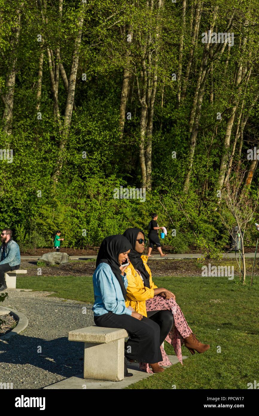 Two women wearing hijabs sitting on bench in park, Seattle, Washington, USA - Stock Image