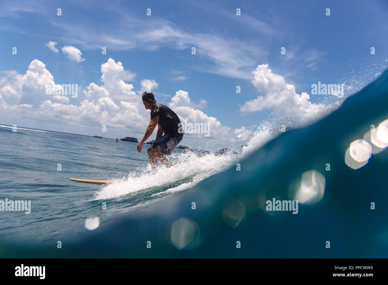 Male surfer riding wave against clouds, Male, Maldives - Stock Image
