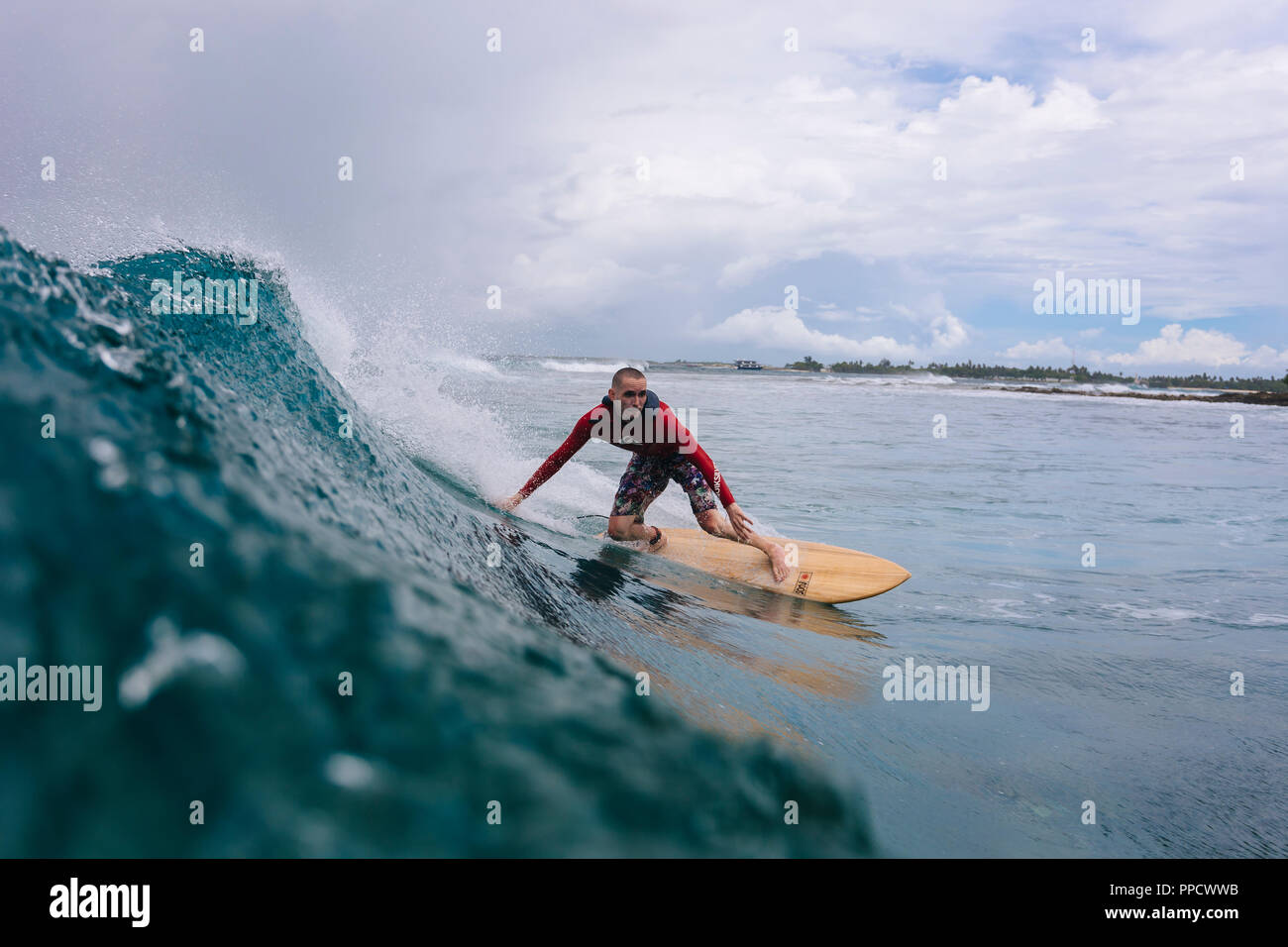 Large clouds over male surfer riding wave, Male, Maldives - Stock Image