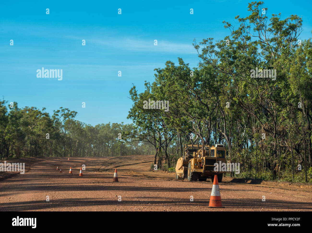 Road construction on a dust road leading through a eucalyptus forest, Litchfield, Australia, NT - Stock Image