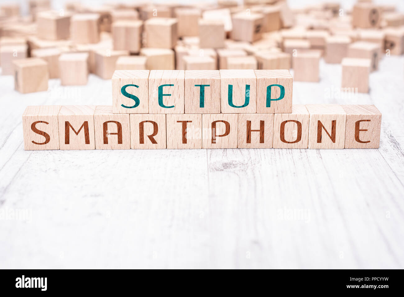 The Words Setup Smartphone Formed By Wooden Blocks On A White Table - Stock Image