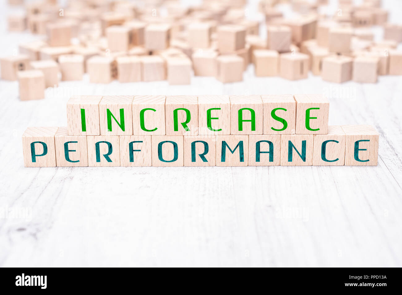 The Words Increase Performance Formed By Wooden Blocks On A White Table - Stock Image