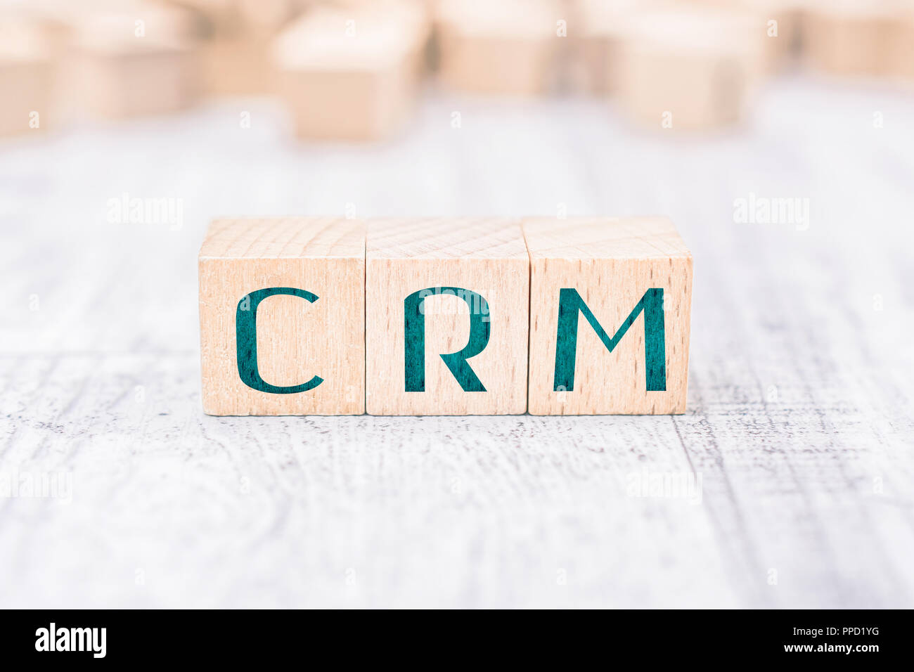 The Abbreviation CRM Formed By Wooden Blocks On A White Table - Stock Image