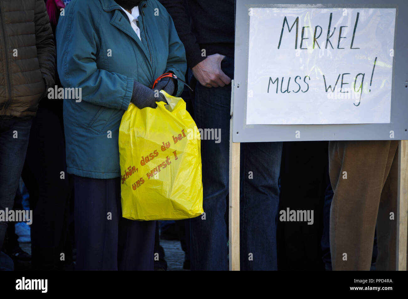 Russian Germans gather in the town square of Traunreut to demonstrate against the refugee policies of Angela Merkel, the Islam and the alleged lying press. In the picture you can see the slogan 'Nice that you were with us' on a shopping bag, next to banners with the demand 'Merkel must go'. - Stock Image