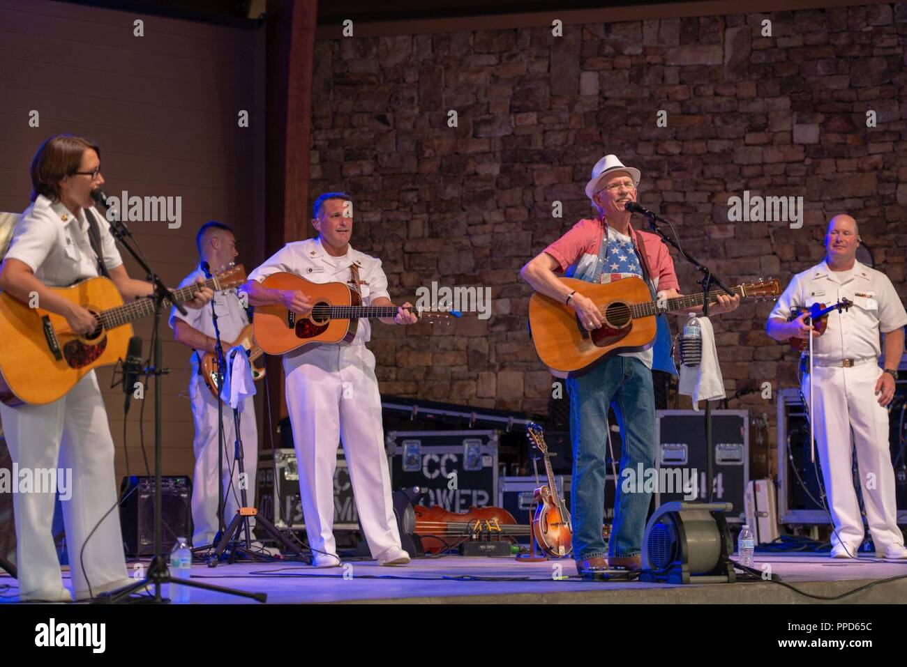 JOHNS CREEK, Ga. (Aug. 31, 2018) The U.S. Navy Band Country Current is joined onstage by a former band member, retired Master Chief Musician Jerry Gilmore, in a performance at the Mark Burkhalter Amphitheater at Newtown Park in Johns Creek, Georgia. Country Current is on a ten-day tour through Virginia, North Carolina, Georgia and Florida, entertaining audiences while connecting Americans to their Navy. - Stock Image