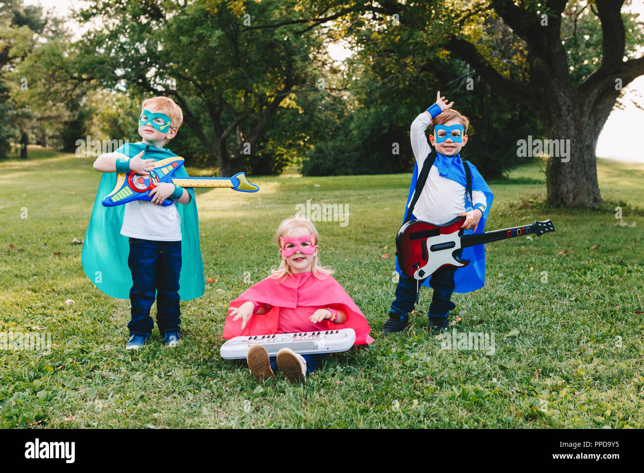 Cute adorable preschool Caucasian children playing superheroes music band rock group. Three kids friends having fun together outdoors in park. Happy a - Stock Image