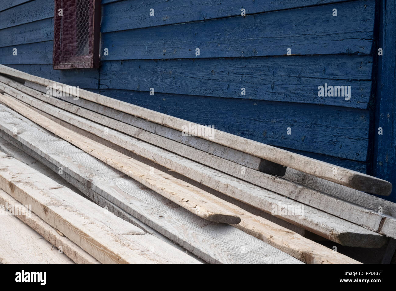 Closeup of blue wooden shed with wooden planks stacked alongside. - Stock Image
