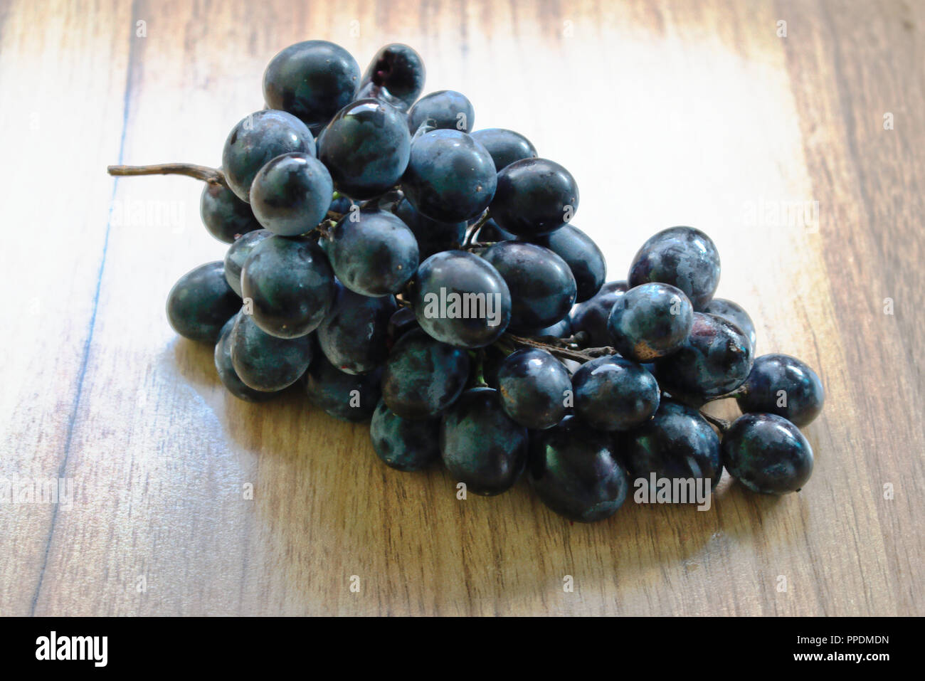 Closeup of grapes on a wooden table - Stock Image